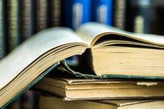 Stapel geöffnete alte Bücher auf hölzerner Tabelle, Volumen im Hintergrund, Lesung, Bildungskonzept Stockbilder