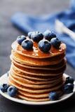 Stapel gebakken Amerikaanse pannekoeken of fritters met bosbessen en honingsstroop op rustieke donkere lijst Heerlijk ontbijt royalty-vrije stock afbeeldingen