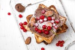 Stapel gebratener Toast mit Schokoladencreme, roter Johannisbeere und Mandeln lizenzfreie stockfotografie