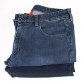 Stapel gefaltete Blue Jeans auf einem weißen Hintergrund Stockfotografie