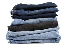 Stapel gefaltete Blue Jeans auf einem weißen Hintergrund Stockbilder
