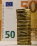 Stapel gefaltete Münzen auf einem Hintergrund einer verblaßten Papierrechnung von f Stockbild