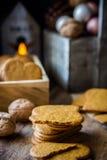 Stapel gehele en gebroken koekjes van de Kerstmispeperkoek in houten doos, aangestoken kaars, denneappels en kleurrijke snuisteri stock foto