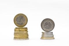Stapel geld euro en zloty muntstukken. De vergelijking van het munttarief stock afbeelding