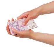 Stapel Geld 200 Ukrainer hryvnia in den weiblichen Händen lokalisiert Stockbilder