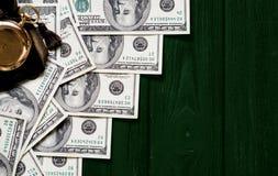 Stapel Gelddollar ausgebreitet wie eine Leiter mit antiker Golduhr auf dunkelgrünem stilisiertem hölzernem Hintergrund Stockbild