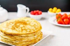Stapel gerade von gemachten heißen russischen Pfannkuchen oder von Blini mit Beeren Stockbild