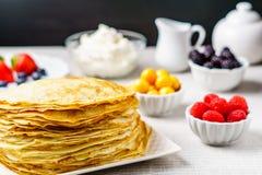 Stapel gerade von gemachten heißen russischen Pfannkuchen oder von Blini mit Beeren Stockbilder