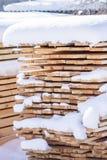 Stapel gesägte Planken bedeckt mit Schnee Lizenzfreie Stockfotos