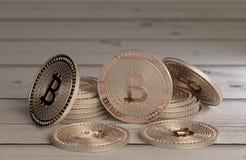 Stapel glänzende kupferne bitcoins als Beispiel für blockchain und Schlüsselwährungsfächer über einem Holztisch Lizenzfreie Stockfotografie