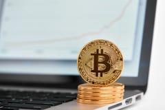 Stapel goldene bitcoins mit einem bitcoin auf seinem Rand, der auf Laptop mit Finanzdiagramm auf seinem Schirm steht Stockbild