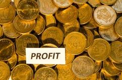 Profitieren Sie Zeichen an einem Stapel goldenen Münzen Stockbilder