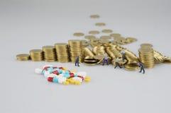 Stapel Goldmünze und Miniaturleute stockfotos