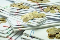 Stapel Goldmünzen auf Stapel von Weiß zerstreute Schreibarbeit Stockbilder