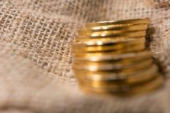 Stapel gouden muntstukken op vage juteachtergrond Stock Afbeeldingen