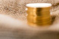 Stapel gouden muntstukken op vage juteachtergrond Stock Fotografie
