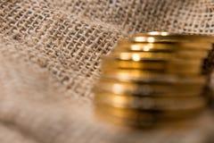 Stapel gouden muntstukken op vage juteachtergrond Royalty-vrije Stock Afbeelding