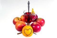 Stapel hete overwogen wijn met appelen en sinaasappelen, kruidnagels en vanillestokken op een witte achtergrond De hete drank van Stock Foto