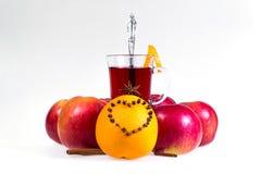 Stapel hete overwogen wijn met appelen en sinaasappelen, kruidnagels en vanillestokken op een witte achtergrond De hete drank van Royalty-vrije Stock Foto
