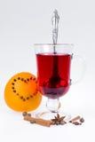 Stapel hete overwogen wijn met appelen en sinaasappelen, kruidnagels en vanillestokken op een witte achtergrond De hete drank van Stock Fotografie