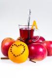 Stapel hete overwogen wijn met appelen en sinaasappelen, kruidnagels en vanillestokken op een witte achtergrond De hete drank van Royalty-vrije Stock Foto's