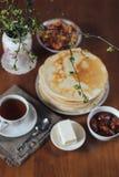 Stapel köstliche selbst gemachte Pfannkuchen oder Blini, Tasse Tee, Butter und Stau Lizenzfreies Stockbild