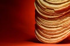 Stapel Kartoffelchips auf Orange Lizenzfreie Stockfotos