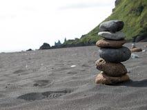 Stapel Kieselsteine am schwarzen Sandstrand im Süden von Island stockfotos