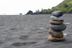 Stapel Kieselsteine am schwarzen Sandstrand im S?den von Island lizenzfreie stockfotos