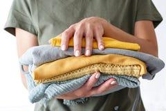 Stapel kleren in geelgroene kleuren in vrouwens handen op witte achtergrond royalty-vrije stock foto's