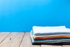 Stapel kleren op houten plank, blauwe achtergrond stock fotografie