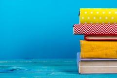 Stapel kleurrijke boeken, grungy blauwe achtergrond, vrije exemplaarruimte Stock Afbeeldingen