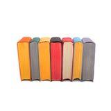 Stapel kleurrijke die boeken op witte achtergrond worden geïsoleerd Zeven hardcovervolumes rode zwarte gele pagina's stock fotografie