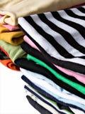 Stapel kleurrijke kleren stock afbeeldingen