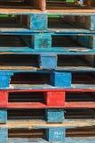 Stapel kleurrijke pallets die op een lading wachten stock fotografie