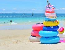 Stapel kleurrijke zwemmende ringen op het strand in Thailand Stock Afbeelding