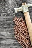 Stapel Kupfer nagelt Tischlerhammer auf hölzernem Brett Lizenzfreies Stockbild