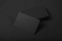 Stapel leere schwarze Visitenkarten auf Textilhintergrund Stockfotografie