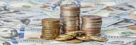 Stapel Münzen auf den zerstreuten Anmerkungen von Dollar auf einem glänzenden Hintergrund stockfotos