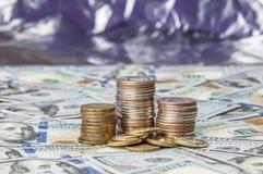 Stapel Münzen auf den zerstreuten Anmerkungen von hundert Dollar auf einem glänzenden Hintergrund stockfoto