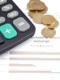 Stapel Münzen, ein Taschenrechner auf den Finanzdiagrammen Stockbild