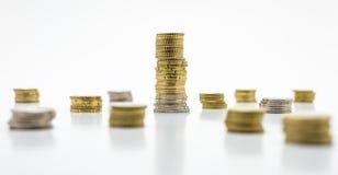 Stapel Münzen, eine große Stange mit Münzen und einige kleine, lokalisiert auf weißem Hintergrund Wachsendes und Rettungsgeldkonz Lizenzfreies Stockfoto
