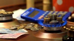 Stapel Münzen stehen in der Flamme eines beleuchtetes Gasbrenners In den Hintergrundmünzen, im Papiergeld und dem Taschenrechner stock footage