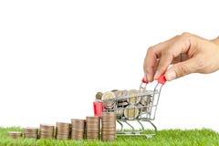 Stapel Münzen und Münzen auf Warenkorb Lizenzfreies Stockfoto