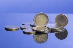 Stapel Münzen von Europa auf nettem blauem Hintergrund mit Reflexion Stockfotos