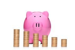 Stapel Münzen vor rosafarbener piggy Querneigung Stockfotografie