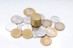 Stapel Münzen, zerstreute Münzen auf weißem Hintergrund lizenzfreie stockfotos