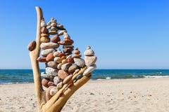 Stapel mehrfarbige ausgeglichene Steine auf alte hölzerne Baumstümpfe, auf einem blauer Himmel- und Seehintergrund Stockfotos