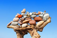 Stapel mehrfarbige ausgeglichene Steine auf alte hölzerne Baumstümpfe, auf einem Hintergrund des blauen Himmels Lizenzfreies Stockfoto