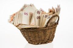 Stapel mit fünfzig Eurobanknoten Geldbündelstapel Bill und brauner Korb Eurohaufen Stockbild